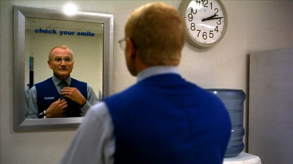 "Robin Williams adjusting his tie in the mirror underneath a sign reading ""Check your smile."""
